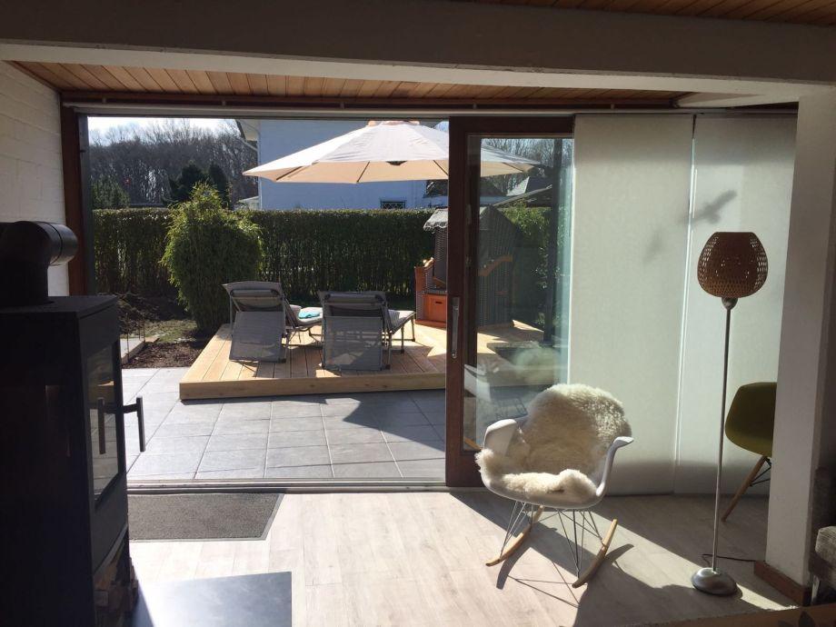 Große Schiebetüren verbinden Wohnzimmer und Terrasse