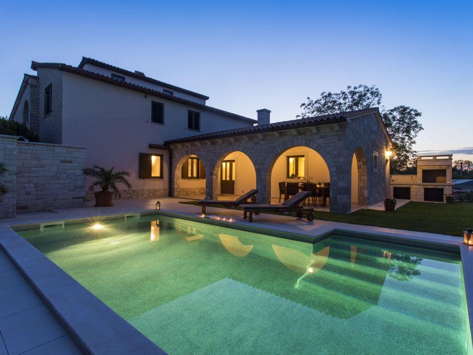 Nachtfoto des Ferienhauses und Pool