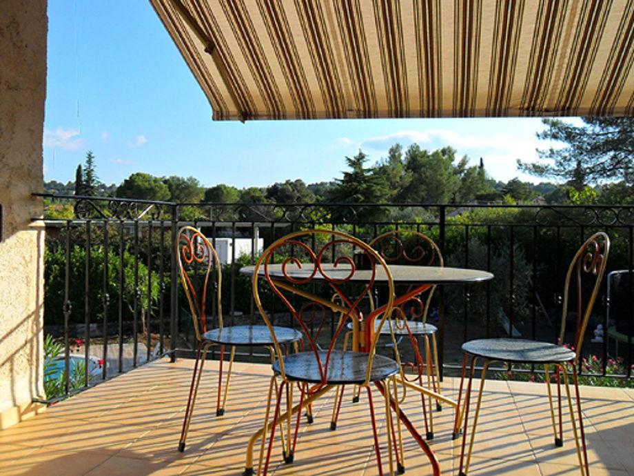 Sonniger Balkon mit Sicht auf den Pool und Garten