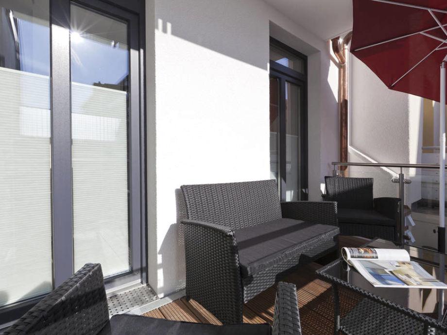 Der Balkon mit Gartenmöbeln und Sonnenschirm