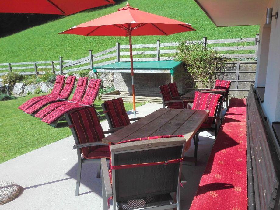 Terasse mit Stühlen, Tischen, Bank, Liegen, Schirmen