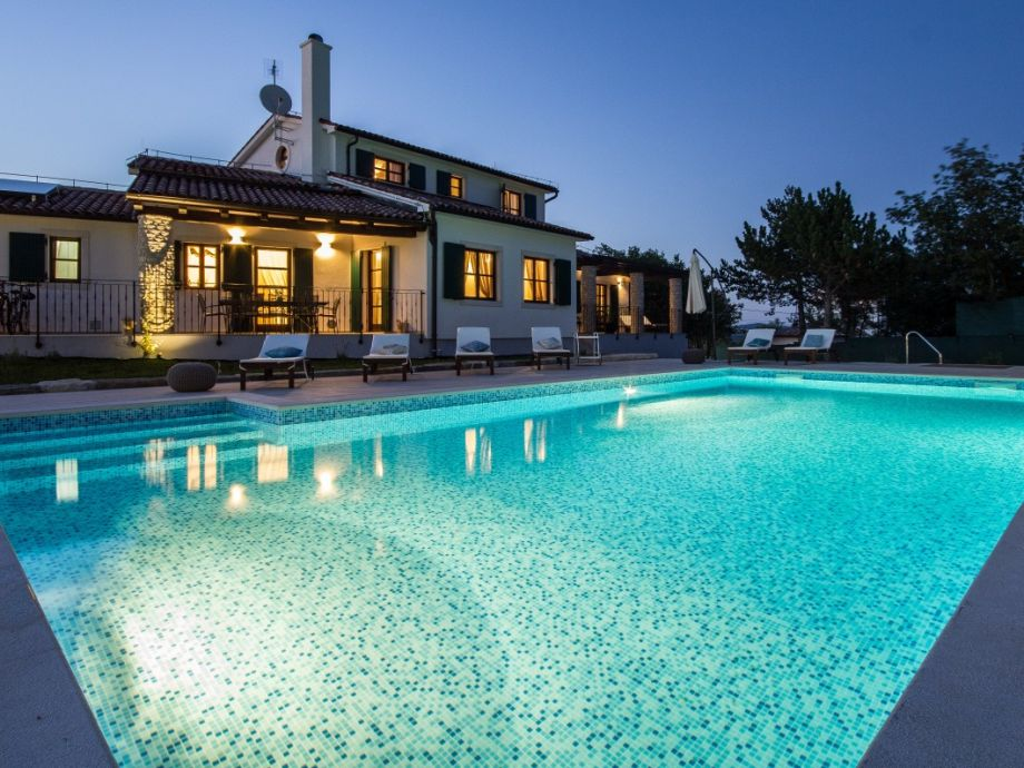 Villa mit großem Pool in der Nacht
