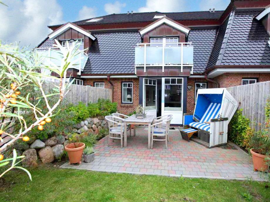 Große, sonnige Terrasse mit Gartenmöbeln und Strandkorb
