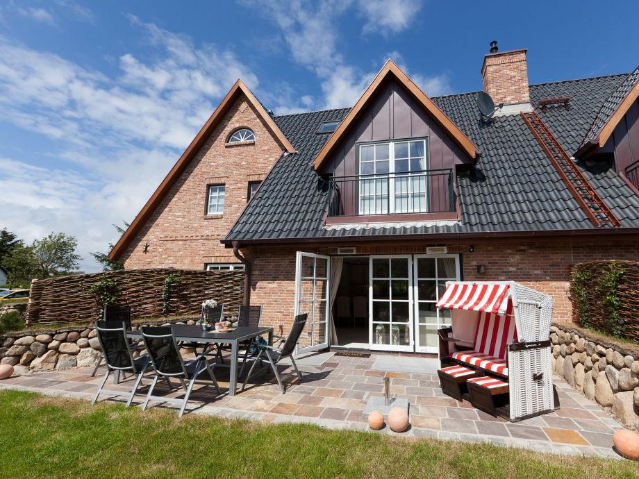 Große, sonnige Terrasse mit Gartenmöbeln