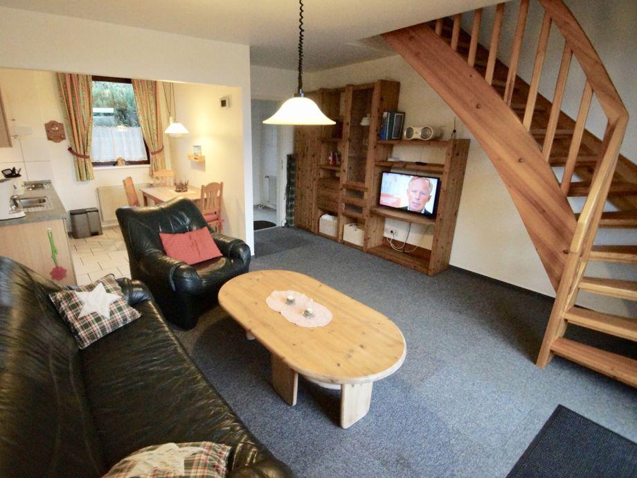 Wohnzimmer mit Flat-TV und Treppe ins OG