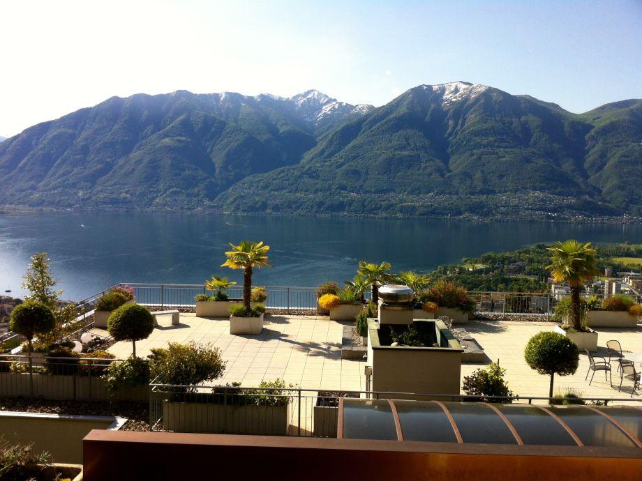Blick vom Balkon auf die Sonnenterrasse, See und Berge