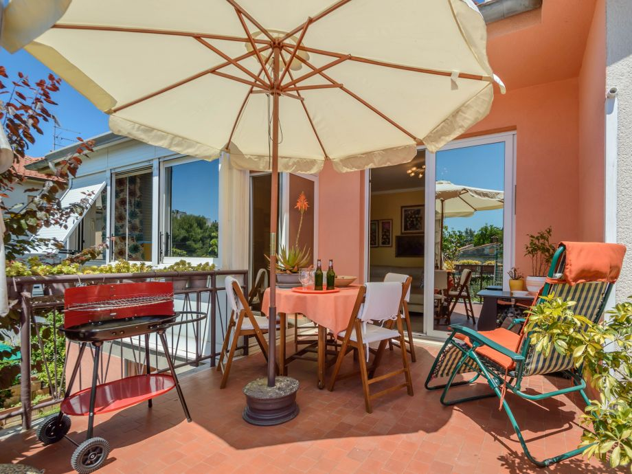 Terrasse mit Esstisch und Grill