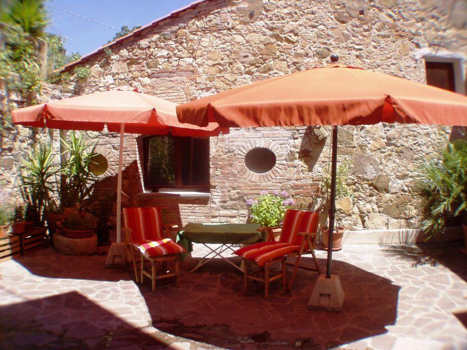 Sonnige Terrasse mit Sonnenliegen und Schirm