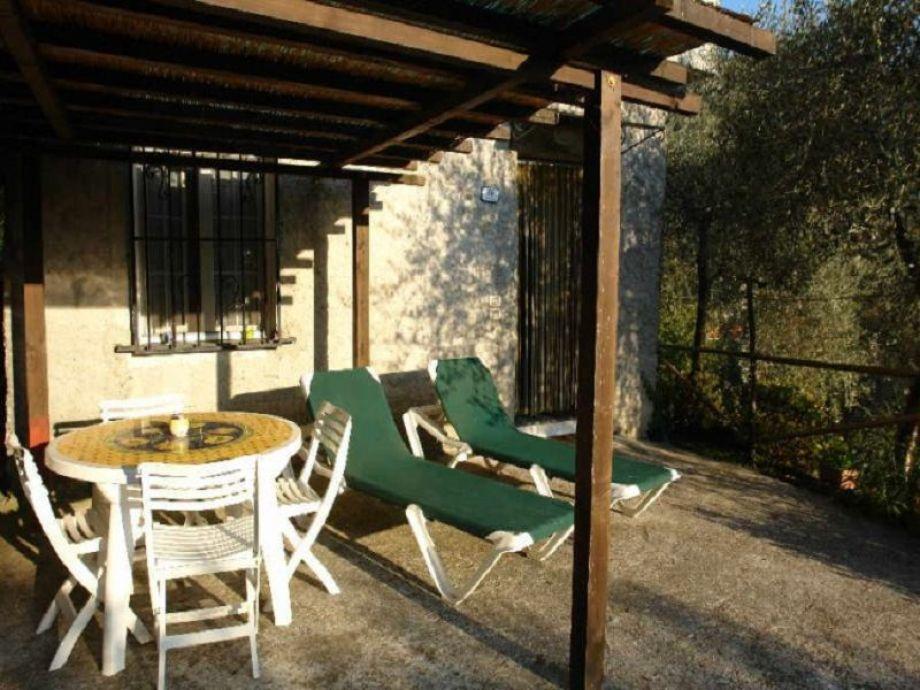 Überdachte Terrasse mit Esstisch und Sonnenliegen