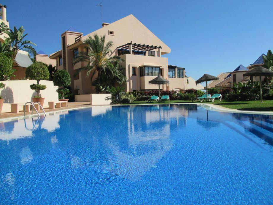 Großer Swimmingpool mit Liegen und Sonnenschirmen