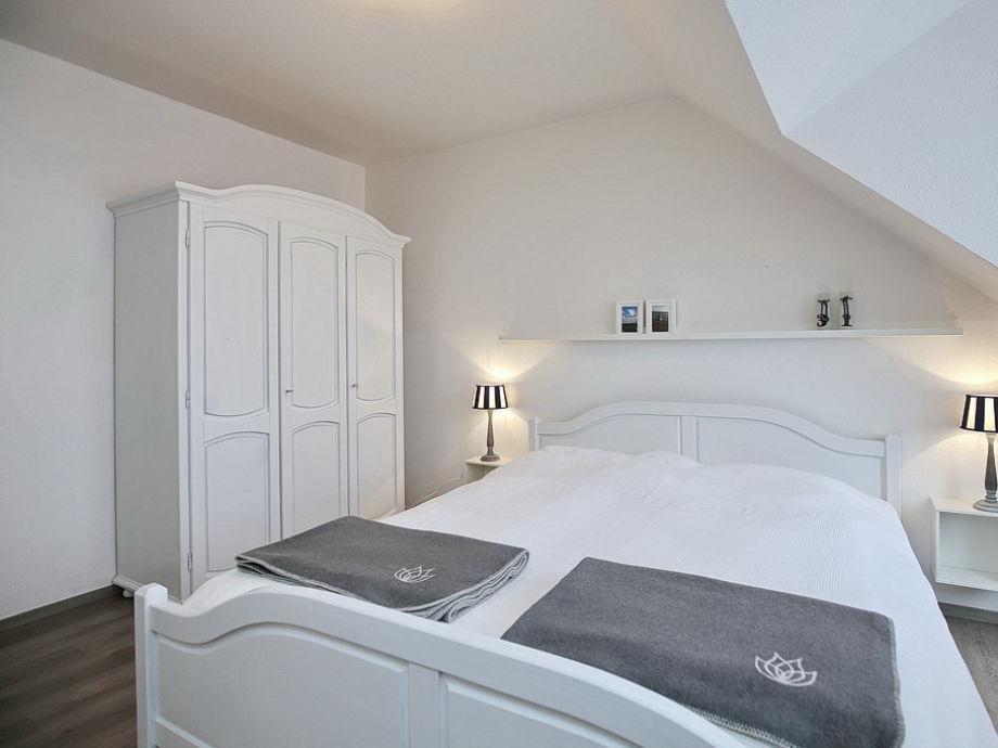 erstes Schlafzimmer mit Doppelbett und Kleiderschrank
