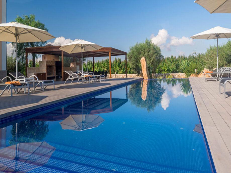 Großer privater Pool mit Sonnenliegen und Schirmen
