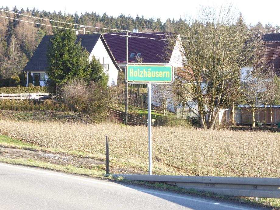 Ortsschild mit Haus im Hintergrund
