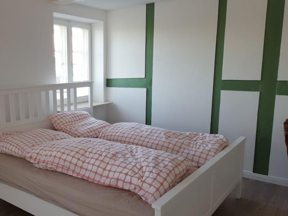Doppelbett an der Fachwerkwand