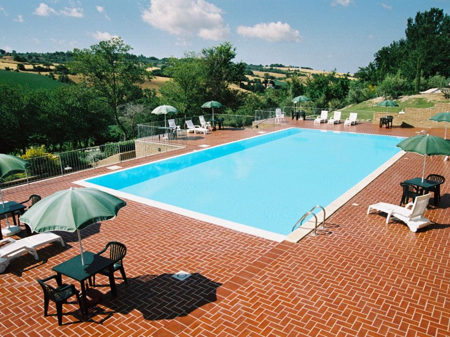 Der Pool mit Sonnenliegen und Esstischen