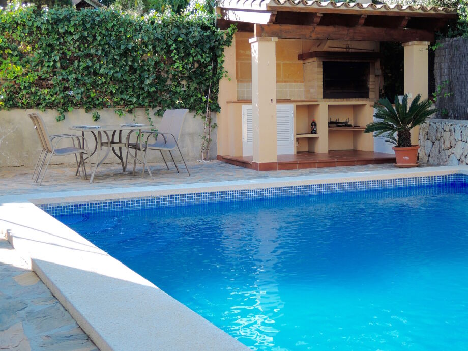 Sonnige Terrasse mit Gartenmöbel und Grillplatz