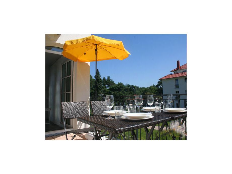 Der Balkon mit Möbeln und Sonnenschirm