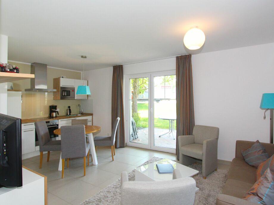 Wohnraum mit Sitzecke, offener Küche und Esstisch