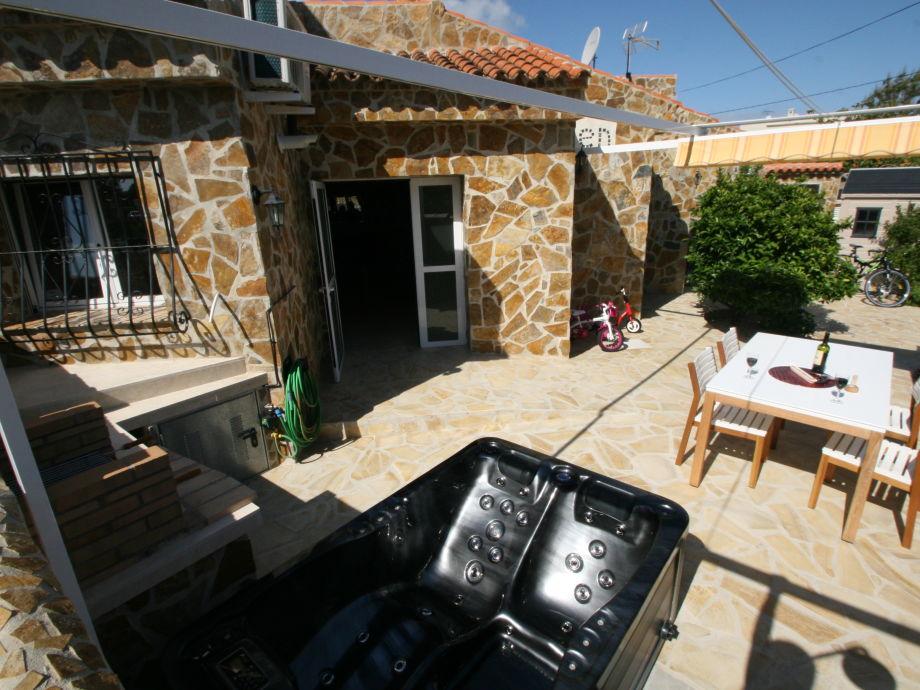 Außenbereich mit Whirlpool und Außenküche mit Grill