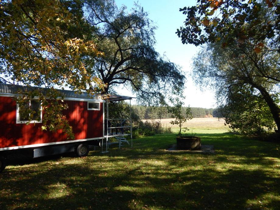 Schäferwagen im Schatten alter Bäume mit Feuerstelle