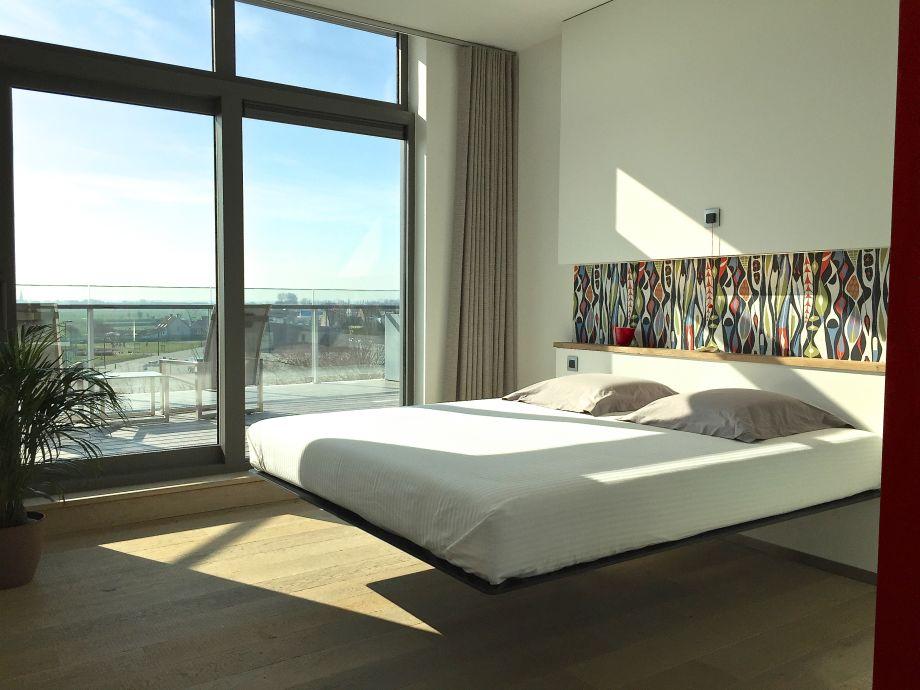 lichtdurchflutetes Schlafzimmer mit Doppelbett