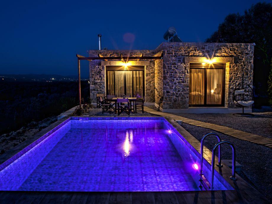 night shot of swimming pool & aromatic garden