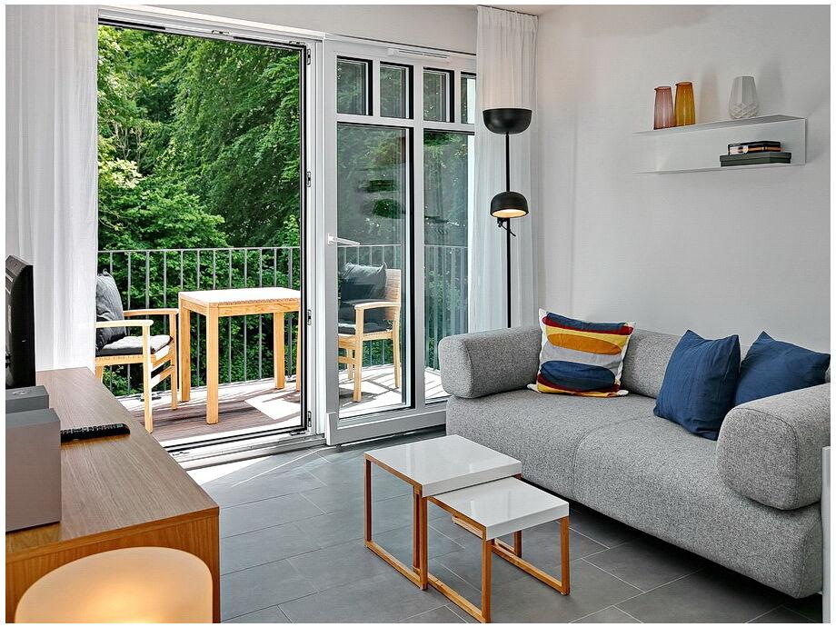 Wohnbereich mit Sofa, Flachbild-TV und Balkon