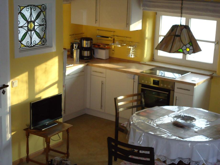 Wohnzimmer mit Fernseher und Küche