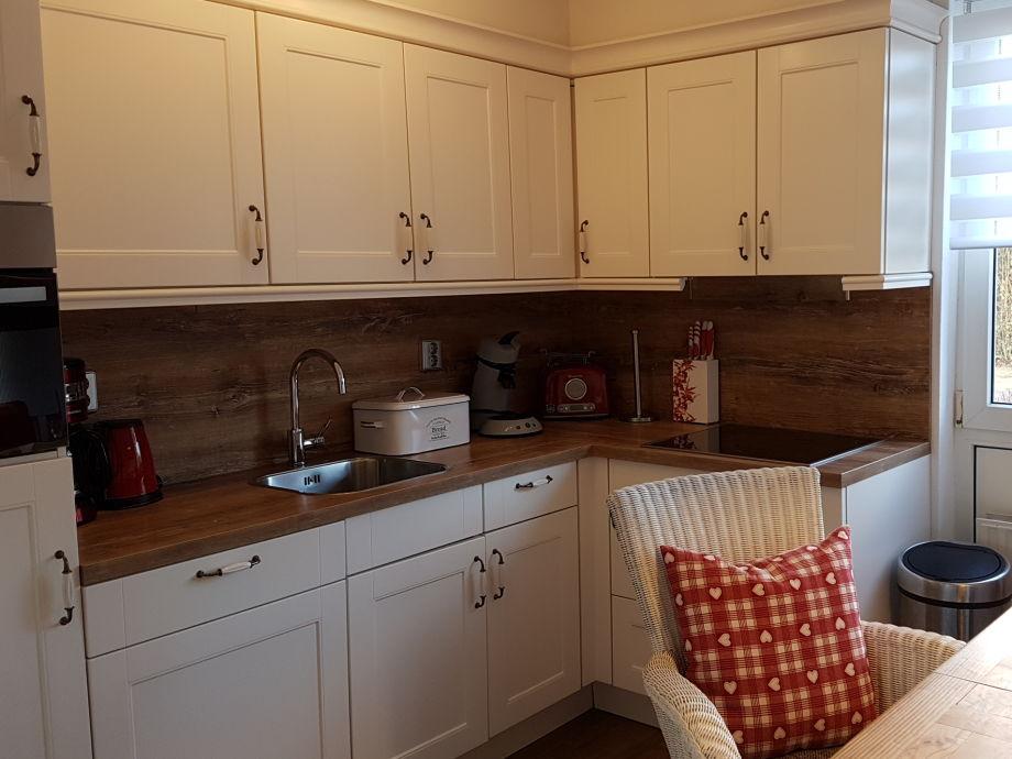 Küche mit Ceranfeld, Spülmaschine, Backofen und Mikrow.