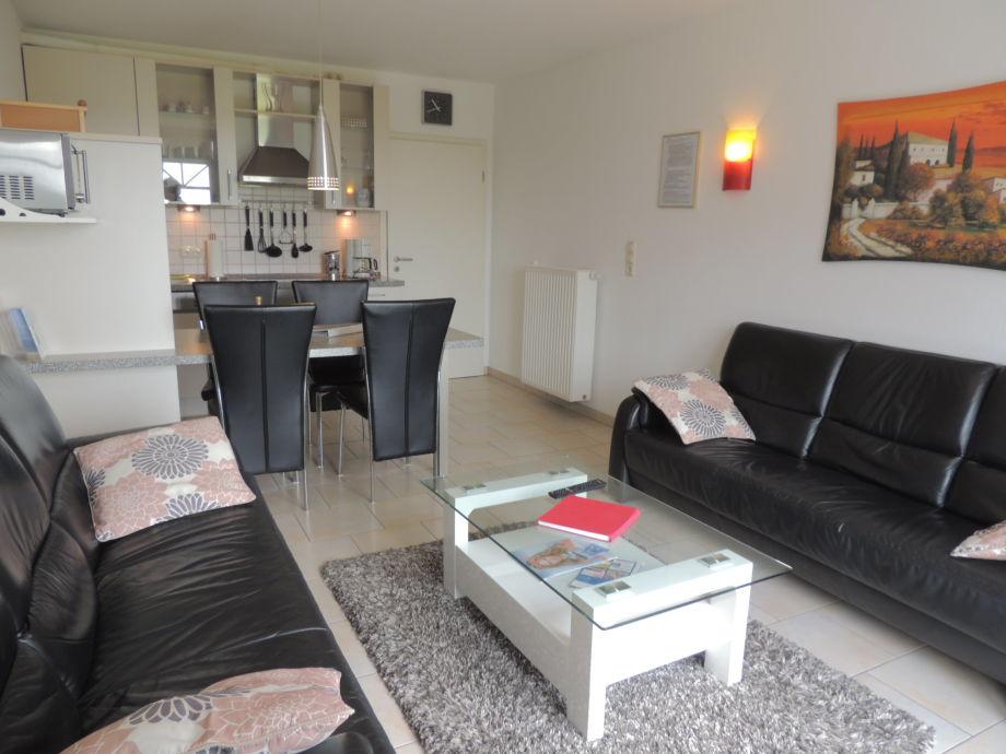 Couchgarnitur mit Esstisch und Küche im Hintergrund
