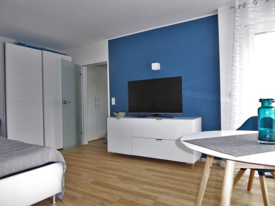 Combined living-sleeping room with large flatscreen TV