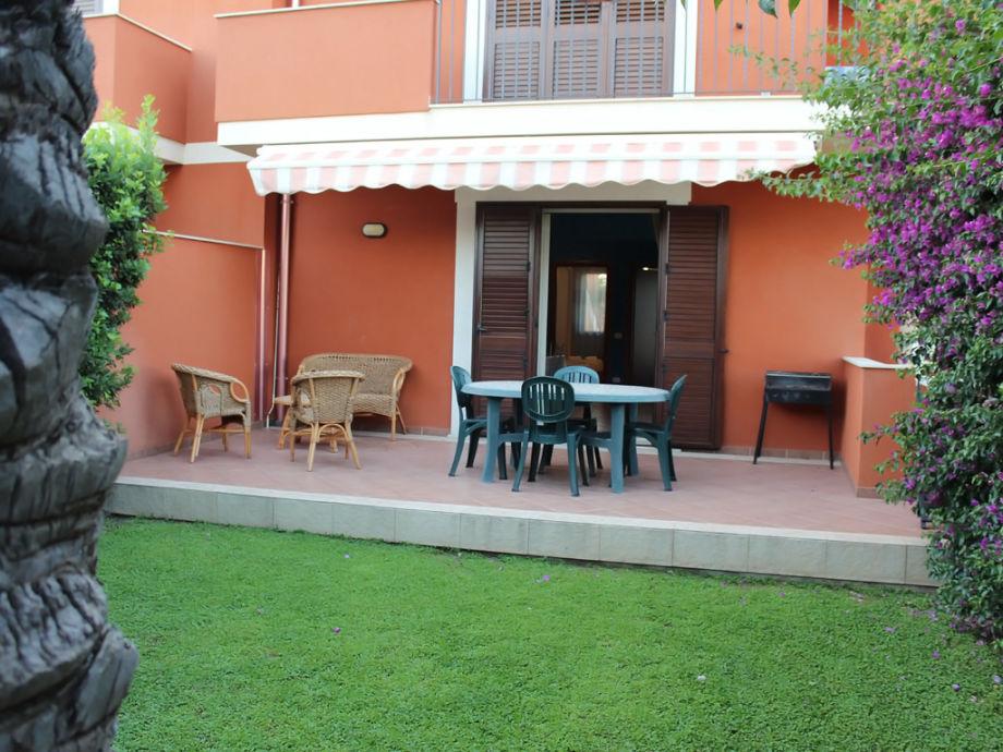 Terrasse mit Gartenmöbeln und Holzkohlegrill