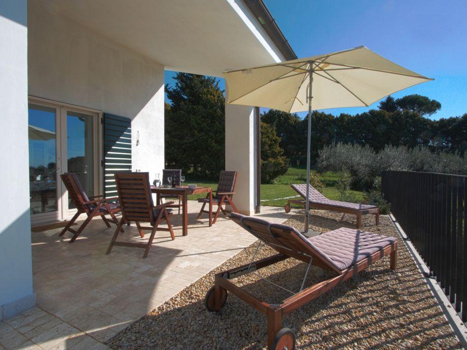 Terrasse mit Esstisch und Liegestühlen