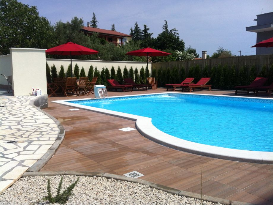 Außenbereich mit Pool, Sonnenliegen und Schirmen