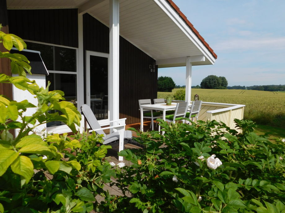 Überdachte Terrasse mit Esstisch, Stühlen und Deckchair