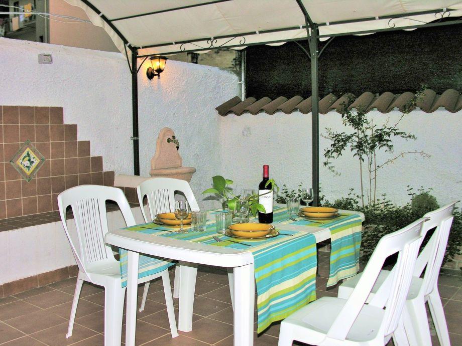 Terrasse mit Esstisch und Laube