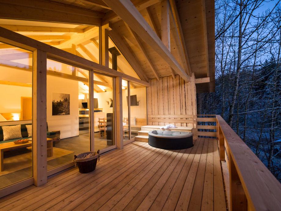 Terrasse mit Badezuber und Bilck in die Forsthütte