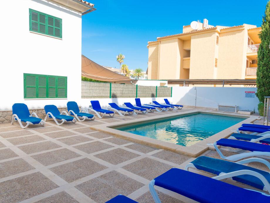 Terrasse mit großem Pool und Sonnenliegen