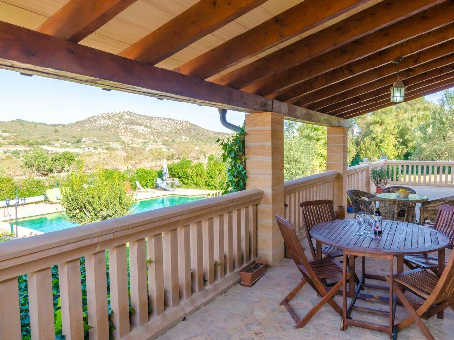 Überdachte Terrasse mit Blick auf Pool und Berge