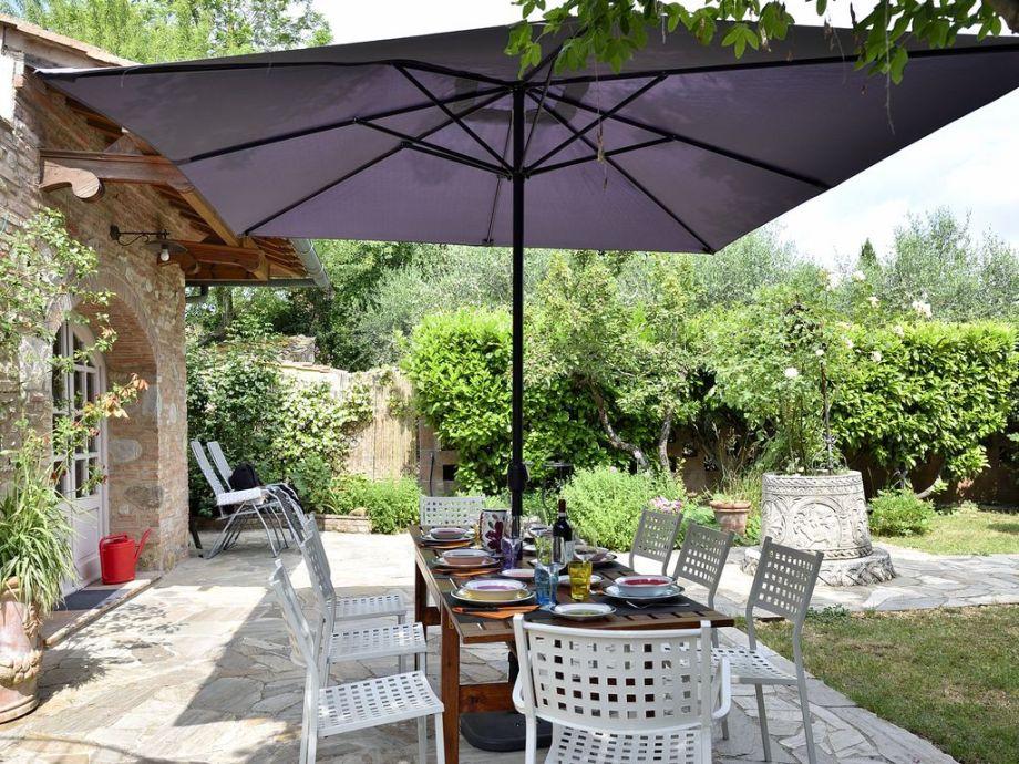 Sonnige Terrasse mit Blick auf den blumigen Garten
