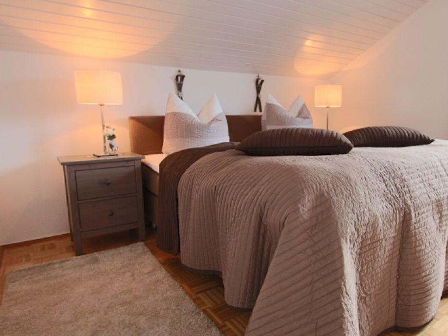 Schlafzimmer mit Boxspringbett und Zugang zum eigenen Balkon