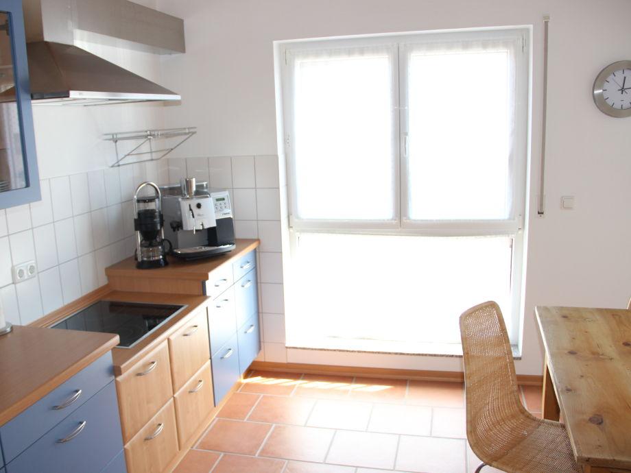 Helle, lichtdurchflutete Küche mit Esstisch und Stühlen