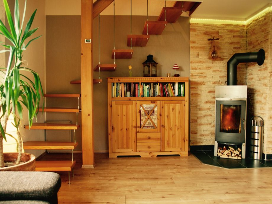 Wohnzimmer mit Kamin und Treppe zur 2. Etage