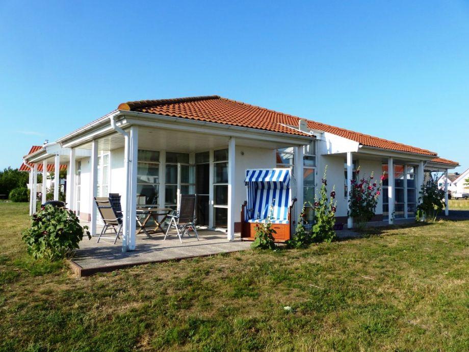 Terrasse mit Strandkorb, Holztisch, Stühle und Grill