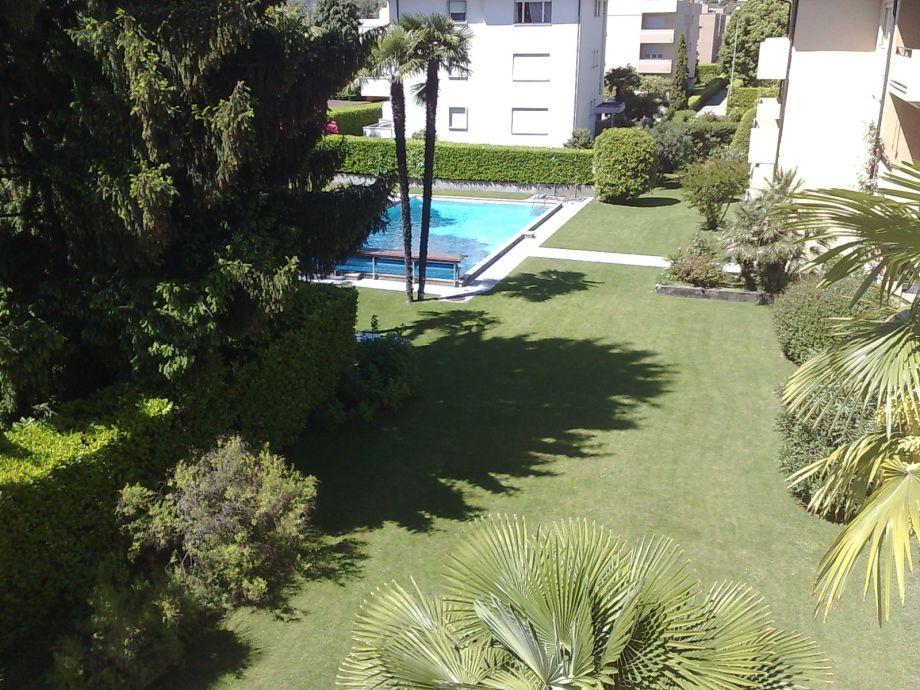 Blick vom Balkon: Pool + Garten