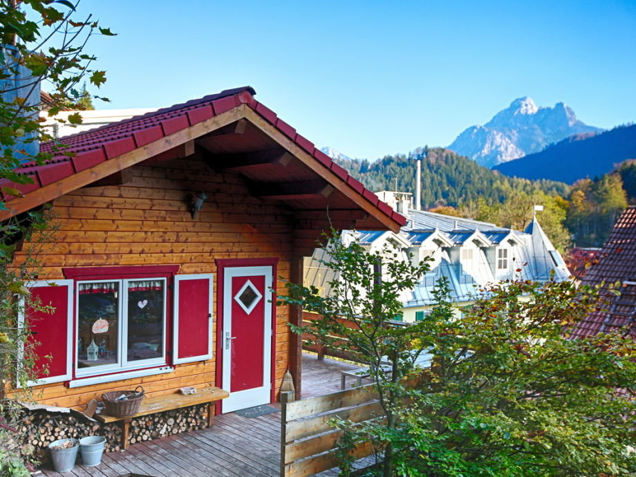 Blockhütte im Hintergrund der Berg Säuling