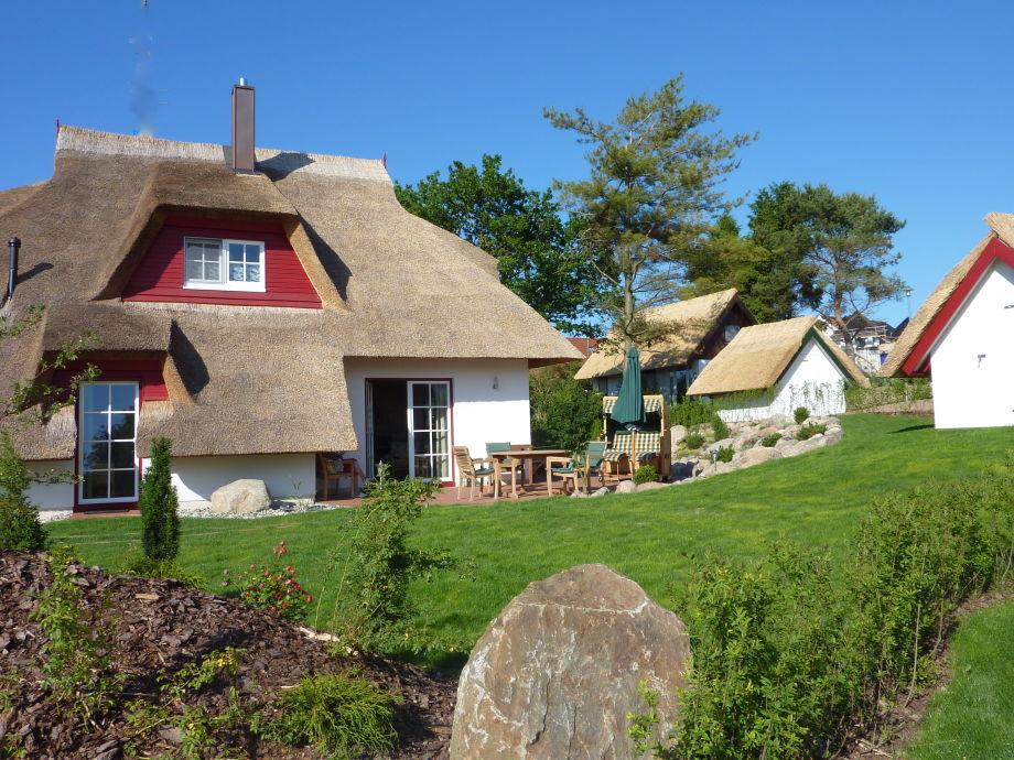 Mit Stein: Blick auf Ferienhaus und Garten.