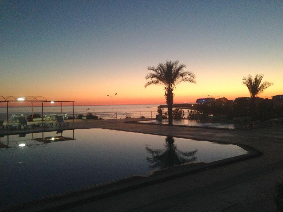 Pool mit Meerblick bei Sonnenuntergang