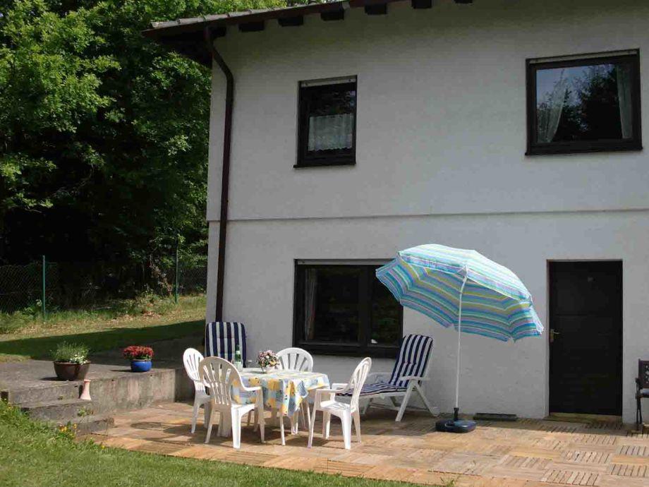 Terrasse mit Gartenmöbeln vor dem Küchenfenster