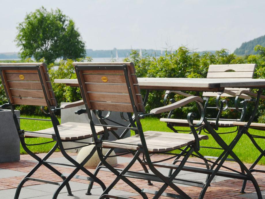 Terrasse mit Sonnenliegen und Blick auf das Wasser